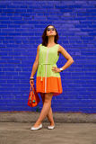 Rich color contrast on a beautiful girl's portrait. Rich contrast of colors by orange, green and violet. Beautiful girl stand in nice fashionable colorful dress royalty free stock image