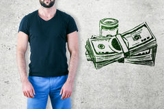 Rich concept. Fit man on concrete background with drawn dollar bills. Rich concept stock photo