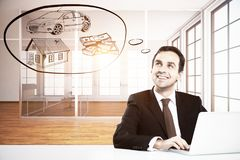 Rich concept. Happy young businessman in modern office using laptop and daydreaming about wealth. Rich concept Stock Image