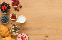 Continental breakfast with croissants and berries on natural wood Royalty Free Stock Images
