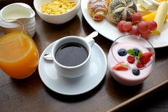 Rich continental breakfast. French crusty croissants, muesli, lots of sweet fruits and berries, hot coffee for morning. Rich continental breakfast. French crusty Royalty Free Stock Photos