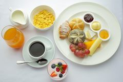 Rich continental breakfast. French crusty croissants, muesli, lots of sweet fruits and berries, hot coffee for morning. Rich continental breakfast. French crusty Royalty Free Stock Photo