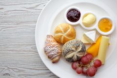 Rich continental breakfast. French crusty croissants, muesli, lots of sweet fruits and berries, hot coffee for morning. Rich continental breakfast. French crusty Royalty Free Stock Photography