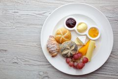 Rich continental breakfast. French crusty croissants, muesli, lots of sweet fruits and berries, hot coffee for morning. Rich continental breakfast. French crusty Stock Photos