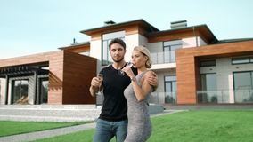 Rich couple drinking champagne near house. Smiling people hugging outside villa. stock video