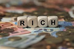 Rich - cube with letters, money sector terms - sign with wooden cubes Royalty Free Stock Images