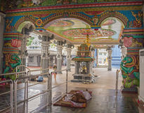 The rich decorated interior of  hindu Temple Shrinivasa Perumal in Singapore. The worshiper is having a rest in the temple Stock Photography