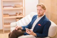 Rich European-Geschäftsmann unter Verwendung des Mobil- oder intelligenten Telefons Stockbild