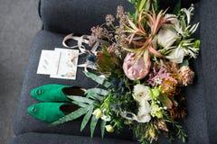 Rich gör grön bröllopbuketten med rosa band på den gråa fåtöljen Gröna brud- skor och berömmande ligga för bröllop nära Royaltyfri Bild