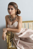 Rich girl on ancient sofa. Elegant brunette girl with rich style posing with elegant pink dress and precious necklace on old sofa in indoor portrait Stock Photo