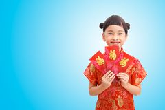 Rich girl in Chinese new year. Chinese Little girl smile with red envelope and wear cheongsam isolated on blue gradient background. Clipping path Stock Photo