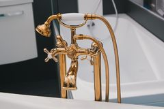 Rich gold plumbing on white bath in the bathroom. Close up view royalty free stock images
