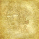 Rich golden Venetian Mask on grunge texture. Golden Venetian mask on golden wallpaper with floral retro elements Royalty Free Stock Images