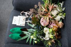Rich green wedding bouquet with pink ribbons on the grey armchair. Green bridal shoes, and a wedding complimentary lying near the. Bridal lush bouquet. Details Royalty Free Stock Image