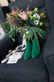 Rich green wedding bouquet with pink ribbons on the grey armchair. Green bridal shoes, and a wedding complimentary lying near the. Bridal lush bouquet. Details Royalty Free Stock Photography