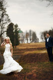 Rich groom and bride huggingoutdoor background wall grass warm a Royalty Free Stock Photos