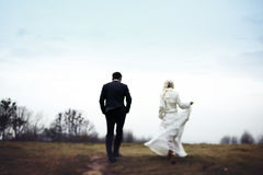 Rich groom and bride huggingoutdoor background wall grass warm a Royalty Free Stock Photo