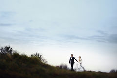 Rich groom and bride huggingoutdoor background wall grass warm a Stock Photo