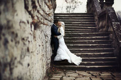 Rich groom and bride huggingoutdoor background wall grass warm a Stock Image