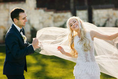 Rich groom and bride huggingoutdoor background wall grass warm a Royalty Free Stock Images