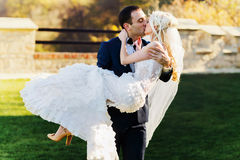 Rich groom and bride huggingoutdoor background wall grass warm a Stock Photos