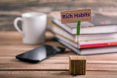 Rich habits sign. Rich habits on wooden sign with book , coffee cup and mobile phone on wooden table Royalty Free Stock Image
