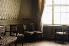 Rich hall with chairs and  big white window in palace. Beatiful rich interior with chairs and  big white big window in palace,  and decorated paper wall with  of Stock Photography