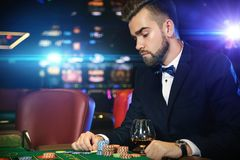 Handsome man playing roulette in the casino. Rich handsome man playing roulette in the casino stock photography