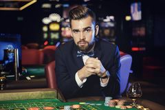 Handsome man playing roulette in the casino. Rich handsome man playing roulette in the casino stock images