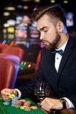 Handsome man playing roulette in the casino. Rich handsome man playing roulette in the casino royalty free stock photo