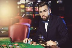 Handsome man playing roulette in the casino. Rich handsome man playing roulette in the casino royalty free stock images