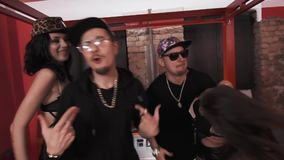 Rich hip hop men in black with girls standing on bed rapping. Rich caucasian hip hop men in black clothes glasses and snapbacks with girls in underwear standing stock footage