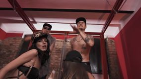Rich hip hop men topless with girls standing on bed rapping. Rich caucasian hip hop men topless glasses and snapbacks with girls in underwear standing on bed stock video footage
