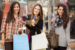 Rich housewives showing their credit cards. Three young housewives shopping together at the mall and showing their credit cards Stock Photography