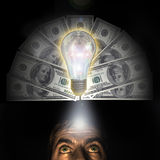 A rich idea. Hundred dollars bank notes   in background of a lighted electric bulb reflecting hundred dollars bank note. The set  symbolizes the birth of an idea Stock Image