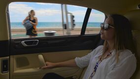 Rich lady riding in expensive car, enjoying trip, luxury vacation in resort city. Stock footage stock footage