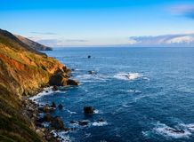 The light of the setting sun illuminates the reds, greens, and browns of the steep mountains and cliffs of the Big Sur coast royalty free stock photography