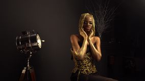 Rich luxurious portrait of african american female model with glossy golden makeup and glossy headwear posing to. Creative luxurious portrait of african american stock video