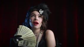 Rich luxurious woman dressed in Gatsby style waves a bundle of dollars like fan