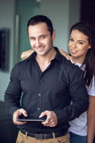 Rich macho man with tablet and sexy girlfriend Stock Photos