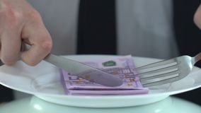 Rich male eating banknotes with fork, concept of consumer society, greedy person. Stock footage stock video footage