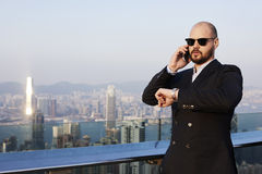 Rich male is talking on mobile phone on a skyscraper roof. Modern man entrepreneur with luxury look is checking time,while having cell telephone conversation Royalty Free Stock Images