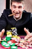 Rich man. Portrait of rich man raking up chips in the casino royalty free stock image