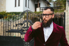 Rich man with a beard smokes cradle. A rich man in a jacket near his house Stock Images