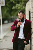 Rich man with a beard smokes electronic cigarette Stock Image