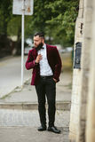 Rich man with a beard smokes electronic cigarette Stock Images