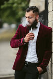 Rich man with a beard smokes electronic cigarette Royalty Free Stock Photo