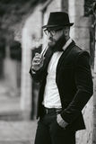 Rich man with a beard smokes electronic cigarette Royalty Free Stock Images