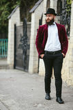Rich man with a beard, thinking about business. A rich man in a jacket near his house stock photo