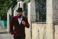 Rich man with a beard, thinking about business. A rich man in a jacket near his house stock photography